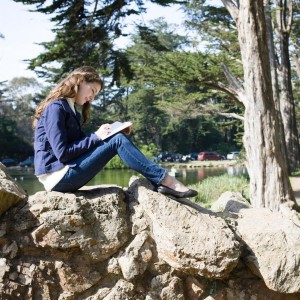 Young Woman Sitting on Rocks in a Park Writing in a Journal
